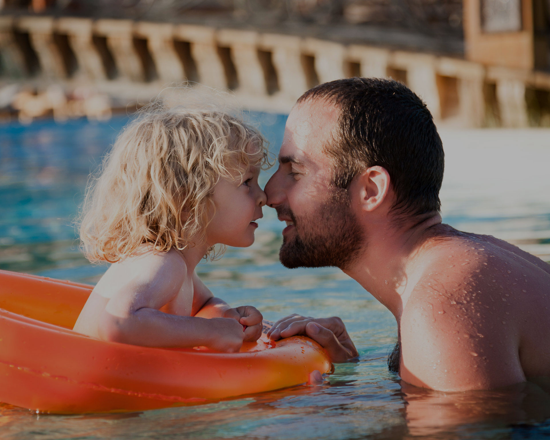 Father and child swimming in pool